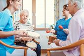 Seniors in nursing home making music with rhythm instruments as musical therapy poster