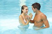 Happy couple celebrating with sparkling wine in swimming pool