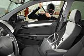 stock photo of mobsters  - A thief wearing a robbery mask trying to steal a purse bag in a automobile - JPG