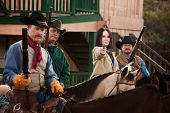 image of hustler  - Old American west woman with pistol and 3 armed men - JPG