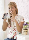 Hispanic woman holding video camera