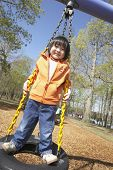 foto of tire swing  - Asian child standing on tire swing - JPG
