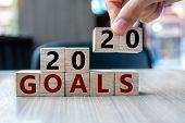 Business Man Hand Holding Wooden Cube With 2020 Goals Word On Table Background. Resolution, Strategy poster