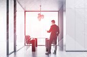 Businessman With Smartphone Standing In Modern Panoramic Dining Room With White Walls, Panoramic Win poster