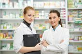 Two cheerful pharmacist chemist woman standing in pharmacy drugstore