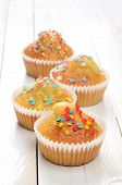 foto of bakeshop  - Delicious homemade muffins over white wooden board - JPG