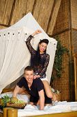 foto of straddling  - Young woman straddled happy man and beats him on bamboo bed in bedroom - JPG