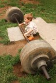 picture of lifting weight  - little boy try lift up the barbell in the park - JPG