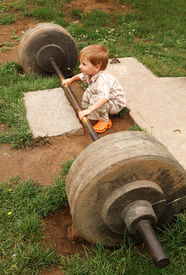 pic of lifting weight  - little boy try lift up the barbell in the park - JPG