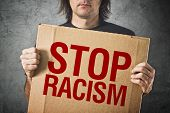 picture of stop hate  - Man holding cardboard banner with STOP RACISM message - JPG