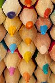 Stack of multicolored pencils tops close up