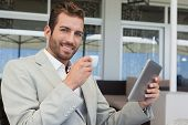 Cheerful young businessman working on tablet drinking espresso in patio of restaurant