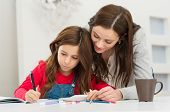 stock photo of innocence  - Happy Young Mother Helping Her Daughter While Studying At Home - JPG