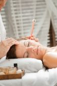 image of ear candle  - Ear candling being carried out on an attractive caucasian woman in a spa - JPG