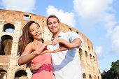 Romantic travel couple in Rome by Colosseum, Italy. Happy lovers on honeymoon showing heart sharped