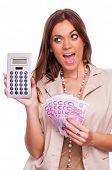 Young business woman looking at calculator and holding fan of five-hundred euro banknotes