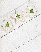 stock photo of linzer  - Overhead view of 3 Christmas linzer cookies with green jelly aranged diagonally on white painted background - JPG