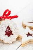 picture of linzer  - Christmas linzer cookies decorated with powdered sugar and with red jam center - JPG