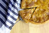 picture of fancy cake  - Caramelised apple tarte tart tartin fancy cake pie on glass plate slice cut off on saple table blue striped cloth - JPG