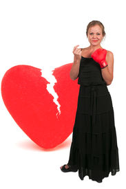 stock photo of heartbreaking  - Beautiful woman in wearing a boxing glove in front of a broken heart  - JPG