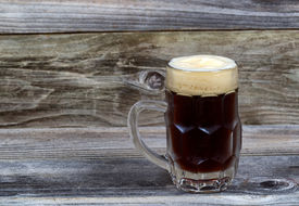 image of stein  - Horizontal image of a glass stein filled with dark draft stout beer on rustic wood - JPG
