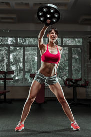foto of swing  - Fitness woman swinging kettle bell at gym - JPG