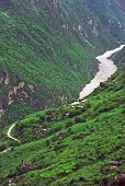 picture of leaping  - vertical vintage style photo of leaping tiger gorge yunnan china -village on mountain side and river winding in the canyon enshrouded with mist
