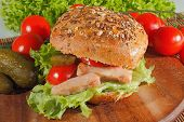 pic of whole-wheat  - Whole wheat bread with fried fillet of chicken garnished with pickled cucumbers tomatoes and lettuce on a wooden board - JPG