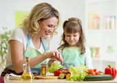 picture of mother child  - mother and child daughter preparing and tasting healthy food - JPG
