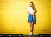 foto of shy girl  - Full Length Portrait of Trendy Hipster Girl Standing at the Yellow Brick Wall Background - JPG