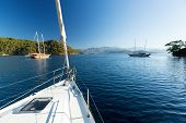foto of sailing vessels  - Sailing vessel anchored in calm bay - JPG