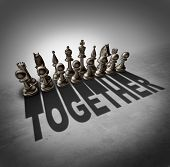 picture of partnership  - Together concept and team effort symbol as a group of chess pieces in a set casting a shadow with the word representing partnership solidarity in a company or union of workers - JPG