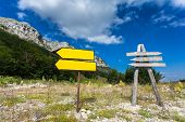 picture of crossroads  - Two signposts on crossroad at mountain and forest - JPG