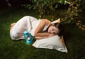 picture of nightgown  - Beautiful young woman in nightgown sleeping on grass at garden at night - JPG