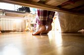 picture of barefoot  - Photo from under the bed on barefoot woman in pajamas at morning - JPG