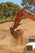 foto of track-hoe  - Track hoe excavator filling up a dump truck at a new commerical construction development