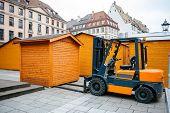 stock photo of stall  - Forklift arranging market stall in public square for carnival public market christmas market - JPG