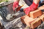 pic of bricklayer  - Bricklayer with brick at a construction site - JPG
