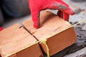 stock photo of bricklayer  - Bricklayer with brick at a construction site - JPG