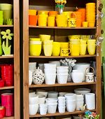 stock photo of planters  - new colored planters in the florist shop - JPG