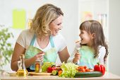 stock photo of cook eating  - mother and kid preparing healthy food and having fun - JPG