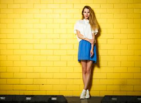 image of shy woman  - Full Length Portrait of Trendy Hipster Girl Standing at the Yellow Brick Wall Background - JPG