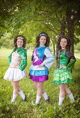 stock photo of wig  - Three young beautiful girls in irish dance dress and wig posing outdoor - JPG
