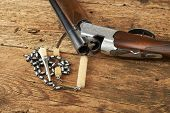 picture of hunt-shotgun  - hunting gun with cleaning kit on a wooden table