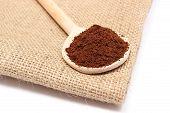 foto of coffee grounds  - Heap of ground coffee on wooden scoop lying on jute canvas coffee grains - JPG