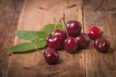 image of cherry  - Sweet cherries with green leaves on wooden table - JPG