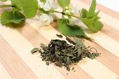 stock photo of nettle  - Heap of dried nettle and fresh stinging nettle with white flowers in background lying on wooden cutting board - JPG