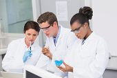 stock photo of concentration  - Concentrated scientists working together in laboratory - JPG