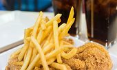 image of food chain  - French fried with crispy fried chicken on white plate near two glasses of cola drink closeup - JPG