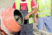 foto of mixer  - Construction worker mixing ingredients in the concrete mixer at building site - JPG